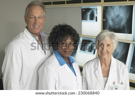 Portrait of three doctors smiling for the camera - stock photo