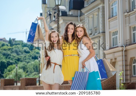 Portrait of three friends. Three friends holding shopping bags and raise their hands and purchase up outside the shop. Smiling girlfriends having fun together walking on the street - stock photo