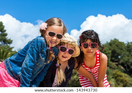 Portrait of three friends together wearing sunglasses outdoors. - stock photo