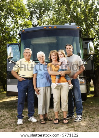 Portrait of three generation Caucasian family standing in front of recreational vehicle smiling and looking at viewer. - stock photo