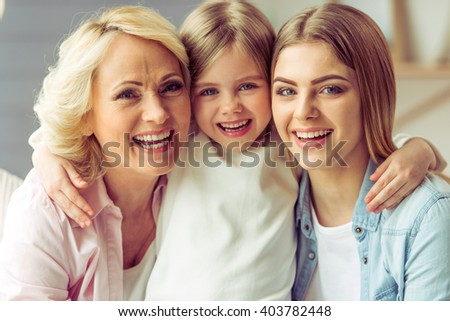 Portrait of three generations of happy beautiful women looking at camera, hugging and smiling - stock photo