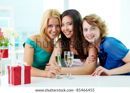 Portrait of three girlfriends sitting in cafe, looking at camera and smiling - stock photo