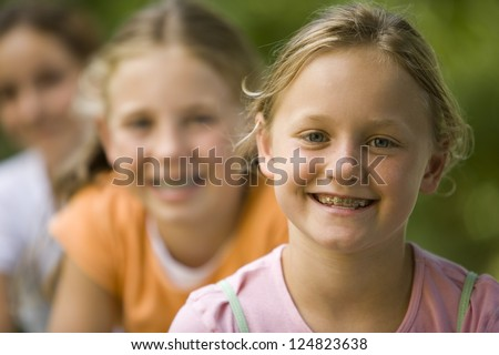 Portrait of three girls outdoors - stock photo