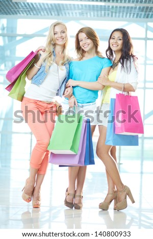 Portrait of three glamorous girlfriends with paperbags looking at camera in the mall