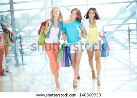Portrait of three glamorous girlfriends with paperbags walking down trade center - stock photo