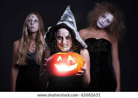 portrait of three halloween personages with orange pumpkin over dark background - stock photo