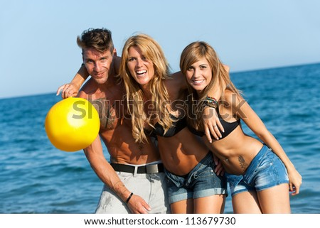 Portrait of three handsome friends embracing on beach.
