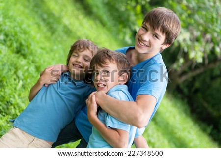 Portrait of three happy brothers in summer park