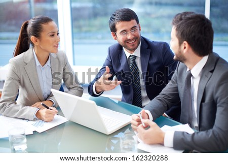 Portrait of three happy co-workers interacting at meeting in office - stock photo
