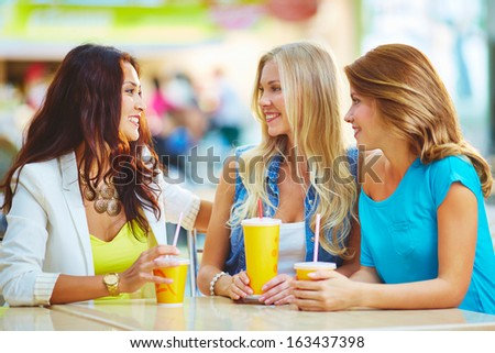 Portrait of three happy girls chatting while having drink after shopping