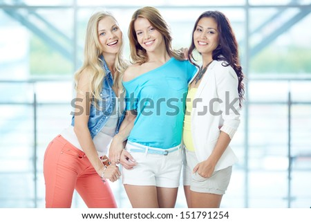 Portrait of three happy girls in smart casual looking at camera - stock photo
