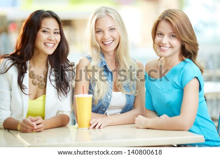 Portrait of three happy girls looking at camera while having drink after shopping - stock photo