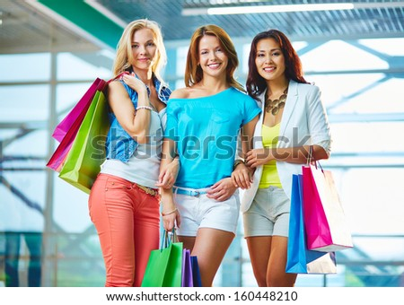 Portrait of three happy girls with paperbags in the mall - stock photo