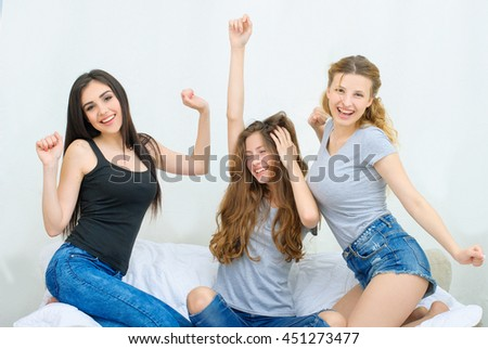 Portrait of three happy pretty young women at home having fun
