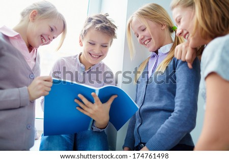 Portrait of three happy schoolgirls looking at notes in exercise book held by schoolboy - stock photo