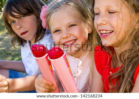 Portrait of three kids enjoying ice pops outdoors.