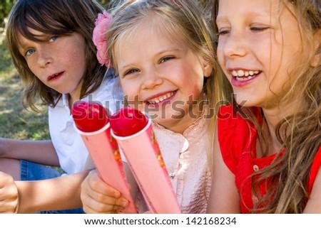 Portrait of three kids enjoying ice pops outdoors. - stock photo