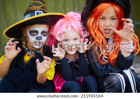 Portrait of three little girls in Halloween costumes looking at camera with frightening gesture - stock photo