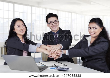Portrait of three member of a multi ethnic business team gathering their hands in the office - stock photo