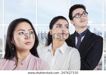 Portrait of three multi ethnic business team standing in a row at office and looking at something - stock photo