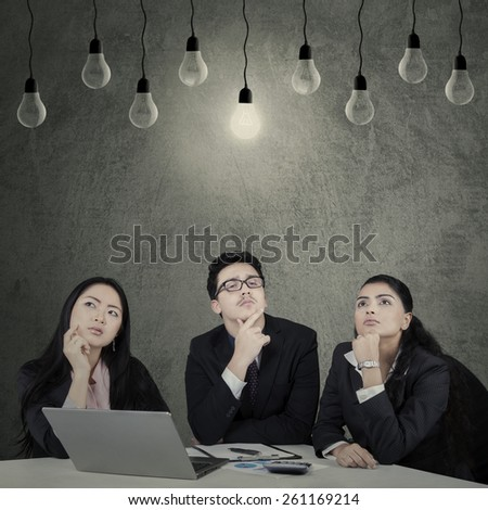 Portrait of three multi ethnic businesspeople with thinking expression to find the solution - stock photo