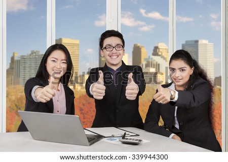 Portrait of three multiracial businesspeople showing thumbs up in the office with laptop on desk - stock photo