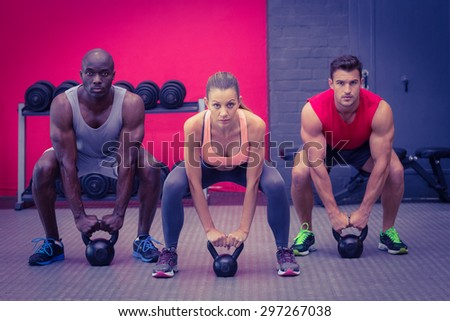 Portrait of three muscular athletes about to lift a kettle bell - stock photo