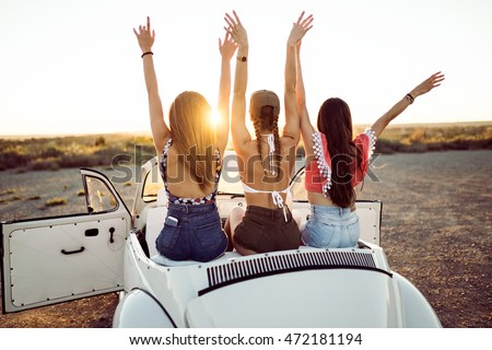 Portrait of three pretty young women driving on road trip on beautiful summer day.
