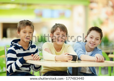 Portrait of three schoolboys sitting at table - stock photo