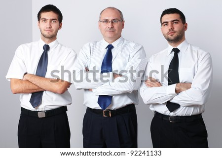 Portrait of three serious businessman with crossed arms - stock photo