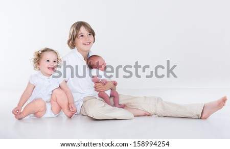 Portrait of three siblings, school age boy, his toddler sister and a newborn baby brother on white background with white clothes