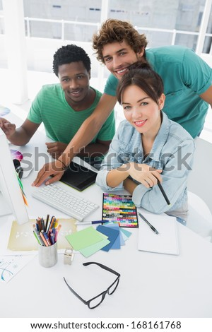 Portrait of three smiling artists working on computer at the office - stock photo