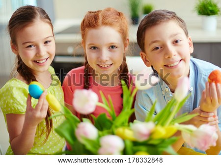 Portrait of three smiling children with Easter eggs - stock photo