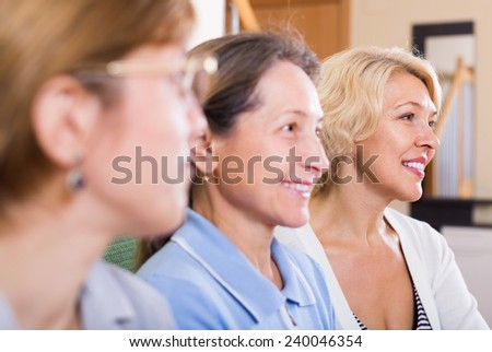 Portrait of three smiling female pensioners in the living room. Focus on blonde