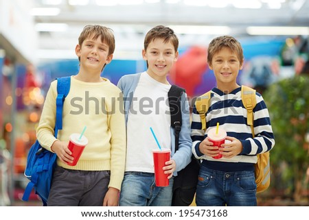 Portrait of three smiling schoolboys with soda - stock photo