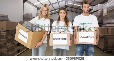 Portrait of three smiling young people with donation boxes against forklift in a large warehouse - stock photo