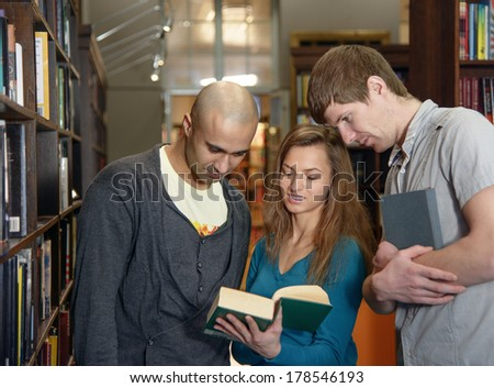 Portrait of three students, european girl and middle eastern and european boy,  standing in a library by a bookshelf and discussing a book