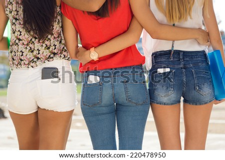 Portrait of three students girls with mobile in the pocket. - stock photo