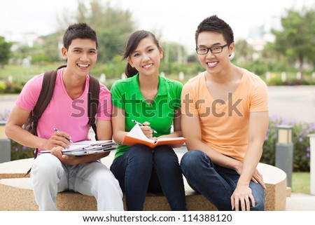 Portrait of three students sitting outdoors in break - stock photo