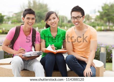 Portrait of three students sitting outdoors in break - stock photo