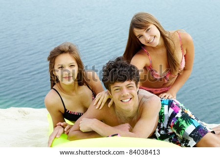 Portrait of three teenage friends spending time by seaside