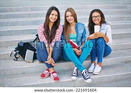 Portrait of three teenage girls sitting on steps - stock photo