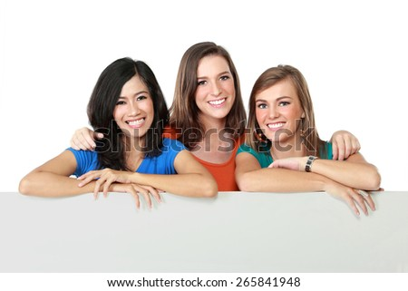 portrait of three teenage girls standing and holding a white board