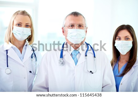 Portrait of three therapeutists in masks looking at camera - stock photo