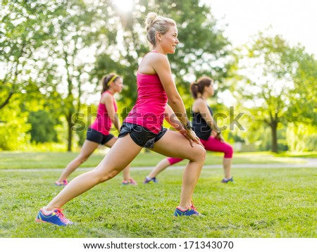 Portrait of three women streching their legs before jogging together - stock photo