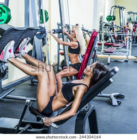 Portrait of three young adult Girls do exercise for legs and hands. in fitness gym on mirror with reflection and window background 3 woman with long blond and brunette hair sitting smiling face - stock photo