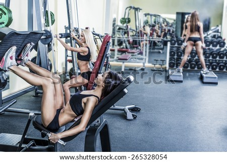 Portrait of three young adult Girls do exercise for legs and hands. in fitness gym on mirror with reflection and window background 3 woman with long blond and brunette hair sitting smiling face