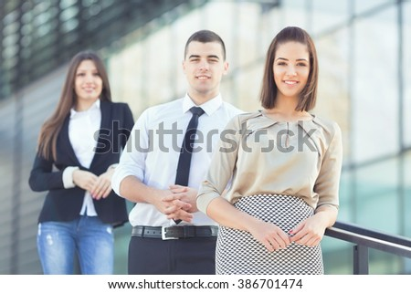 Portrait of three young and successful business people. Focus on confident young businesswoman standing in front of her business team. - stock photo