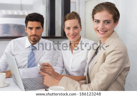 Portrait of three young business people using laptop together at office desk