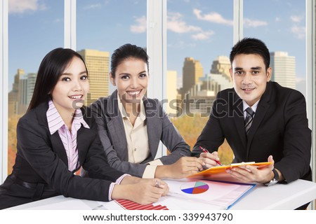 Portrait of three young businesspeople smiling at the camera while meeting in the office with autumn background on the window - stock photo